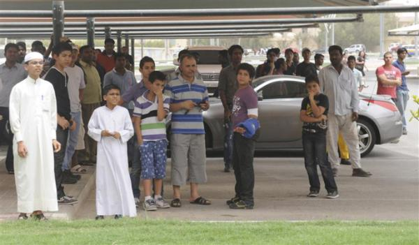 Onlookers watch from a parking lot as a fire broke out at the Villaggio Mall, in Doha's west end.