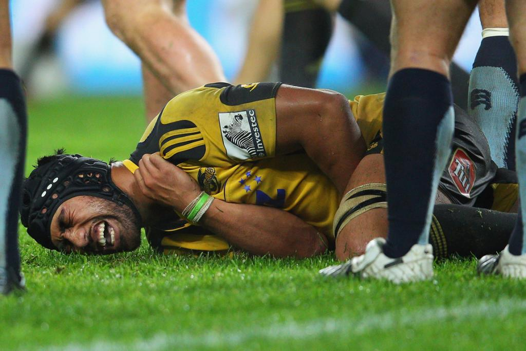 Victor Vito of the Hurricanes grimaces as he holds an injured shoulder against the Waratahs.