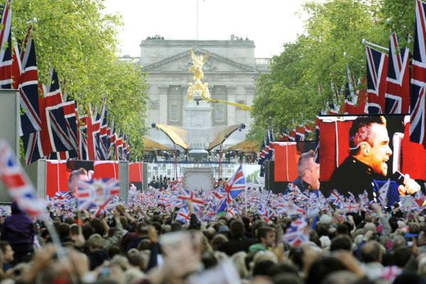 Spectators watch Robbie Williams on giant screens during the Diamond Jubilee concert in front of Buckingham Palace in London.