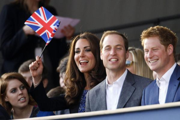 Britain's Catherine, Duchess of Cambridge waves a Union Flag as she sits alongside her husband Prince William and Prince Harry (right) during the Diamond Jubilee concert in front of Buckingham Palace in London.