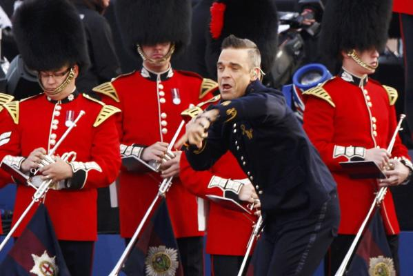 Singer Robbie Williams performs next to the Band of the Welsh Guards during the Diamond Jubilee concert outside Buckingham Palace in London.