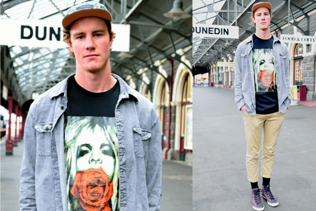 Chris Brun, photographed at Dunedin Railway Station, wearing a Moodie Tuesday t-shirt and an I Love Ugly cap.
