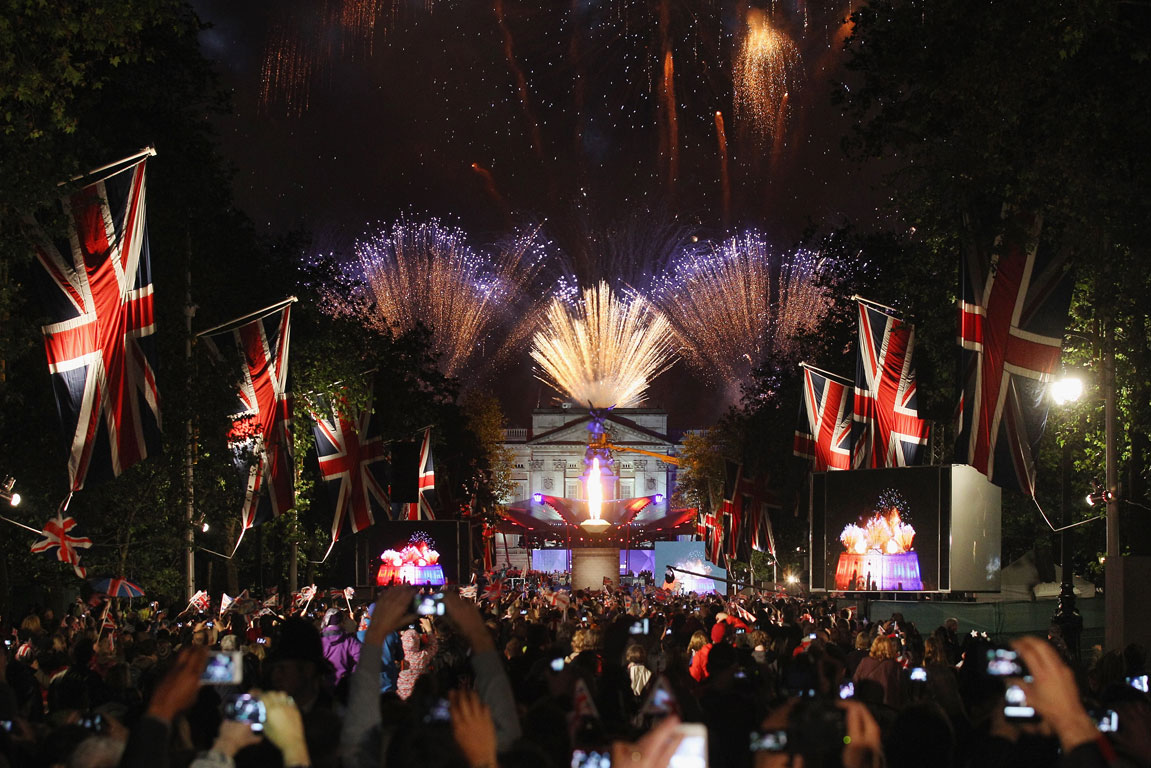 Crowds stand in The Mall as they watch a firework display at the end of The Diamond Jubilee Concert at Buckingham Palace in London.