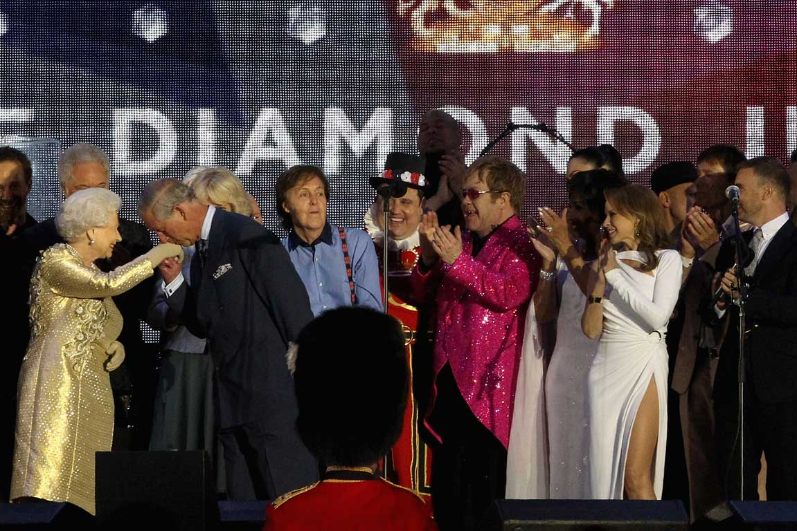 Prince Charles kisses his mother, Queen Elizabeth's hand, while on stage with artists at the end of Diamond Jubilee Concert at Buckingham Palace in London.