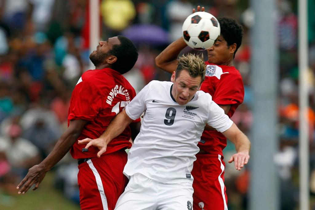 All Whites forward Shane Smeltz goes up to head the ball in front of two New Caledonia players during the semifinal loss at the Oceania Nations Cup.