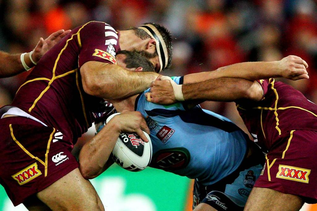 Mitchell Pearce is tackled over the top by Dave Taylor.