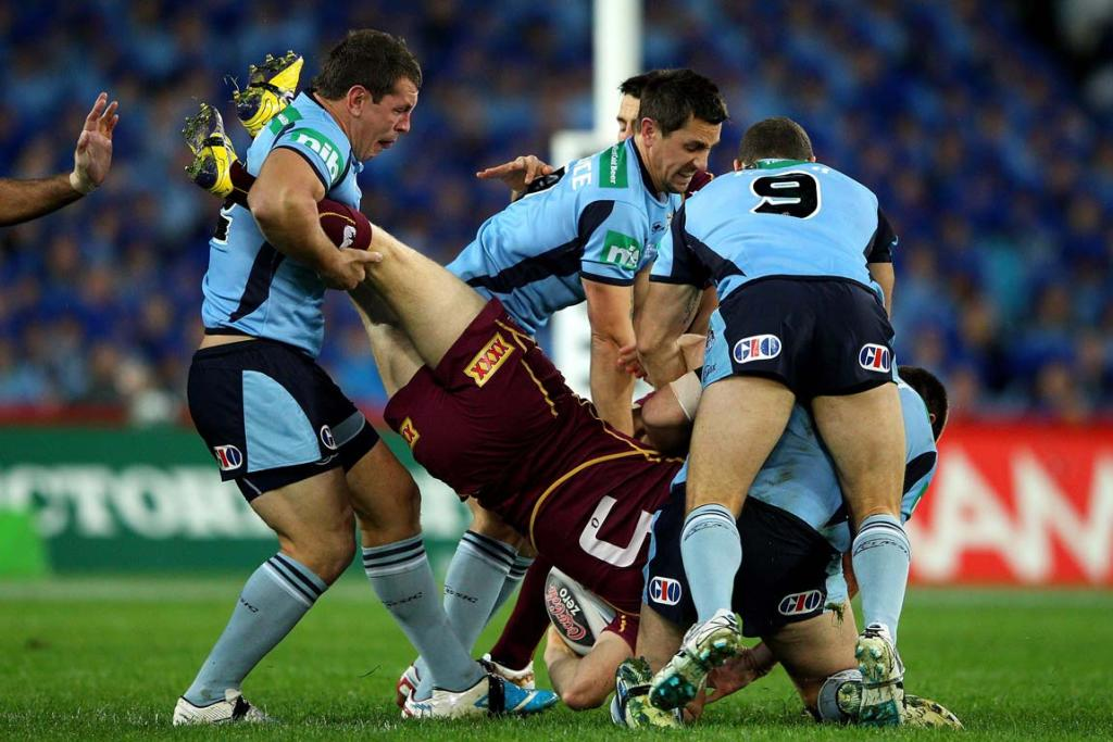 Queensland wing Brent Tate is lifted and dumped in the tackle by three Blues players.