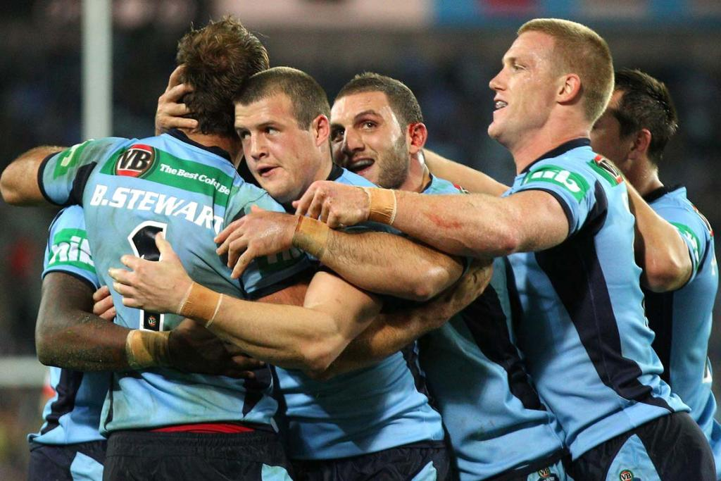 New South Wales players swarm Brett Stewart after one of his two tries.