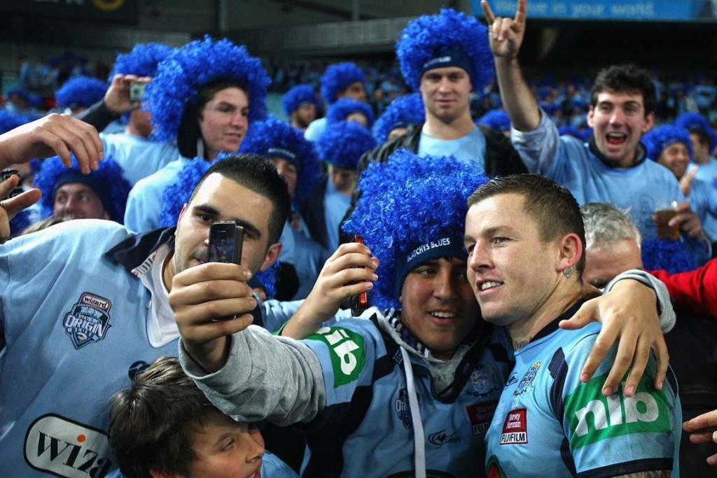 NSW halfback Todd Carney (right) poses for a photo with fans after the victory.