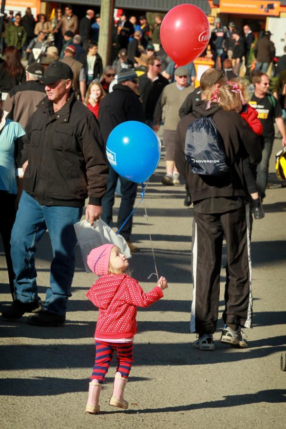 FREEBIE FUN: A young girl attempts to untangle the balloons she has collected as she makes her way through the throngs of people who made the most of the fine opening-day weather.