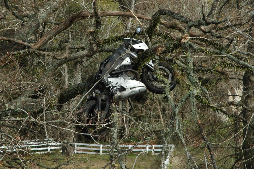 The motorcycle ended up suspended above the ground and the rider in a nearby ditch.