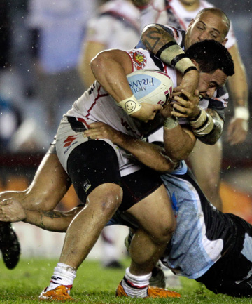 HAULED IN: Konrad Hurrell of the Warriors is tackled by the Sharks defence.
