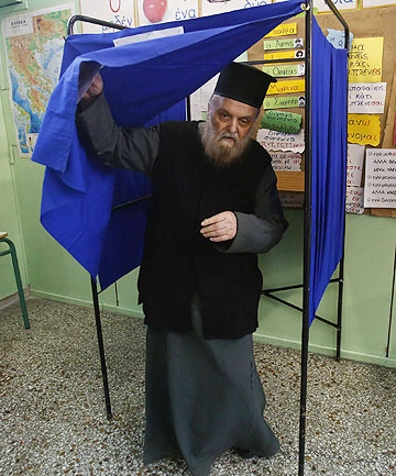 MORE TURMOIL TO COME?: A Greek orthodox priest holds his ballot paper as he exits a voting booth at an Athens school used as a polling station.