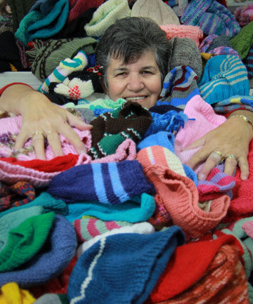 Lots of hats: Knit World New Plymouth assistant manager Diane Lehmann among the 1868 hats knitted by the shop's customers for charity.