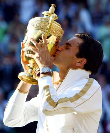 SEARCHING FOR SEVEN: Roger Federer kisses the trophy after the last of his six triumphs at Wimbledon, after an epic five-set victory over Andy Roddick in 2009.