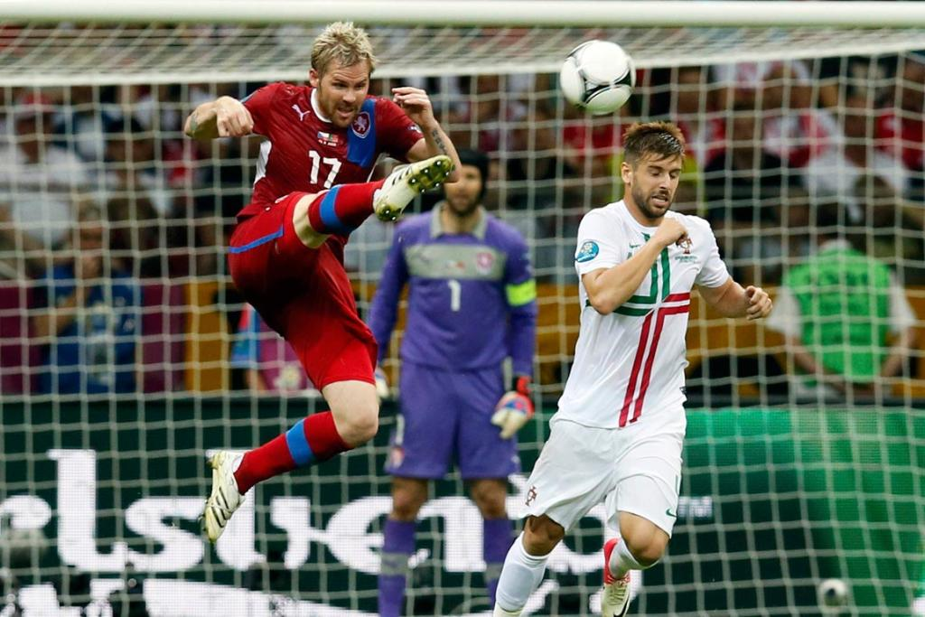 Czech Republic's Tomas Hubschman jumps for the ball next to Portugal's Miguel Veloso during their quarter-final match.