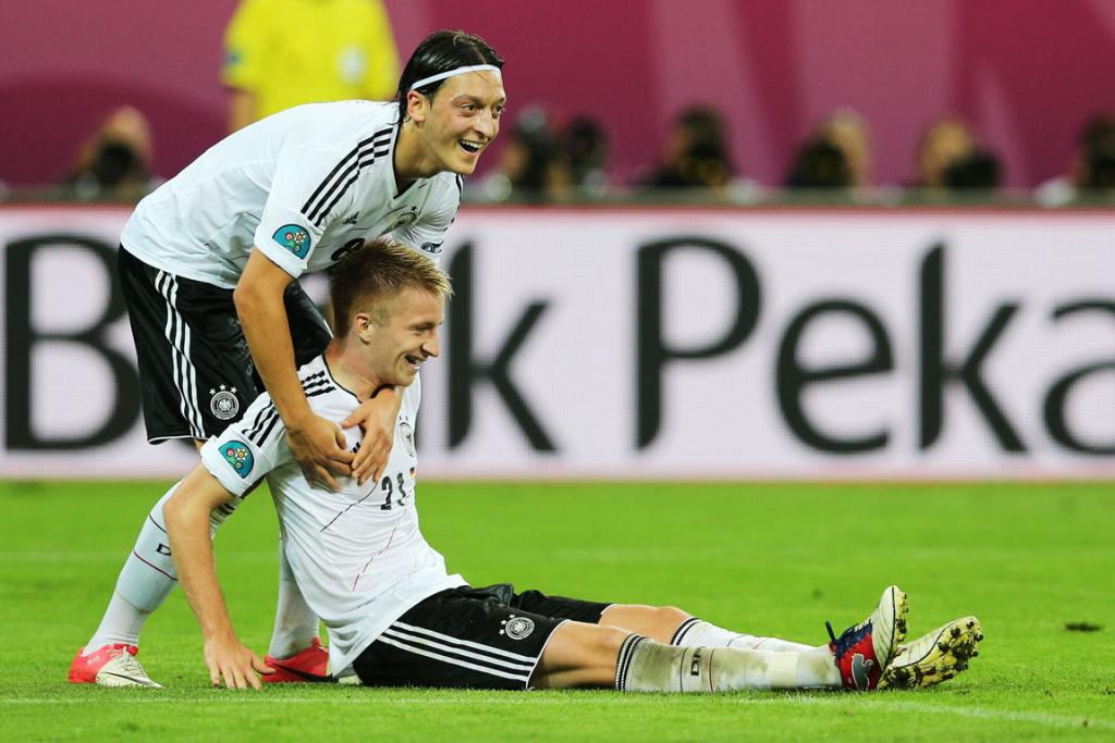 Marco Reus of Germany celebrates scoring their fourth goal against Greece with Mesut Ozil.