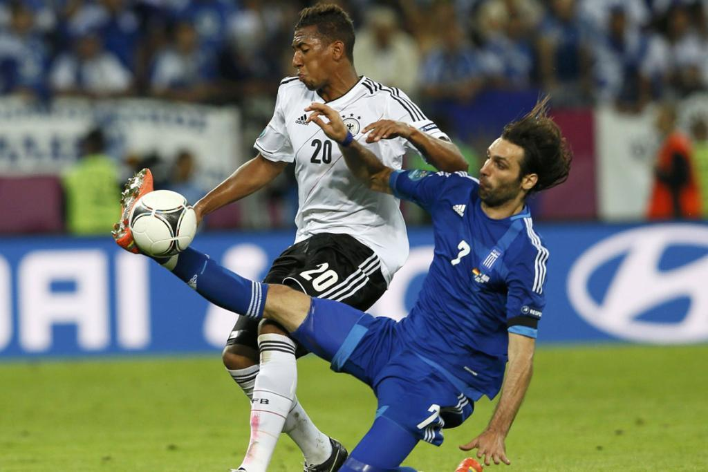 Greece's Giorgos Samaras fights for the ball with Germany's Jerome Boateng.