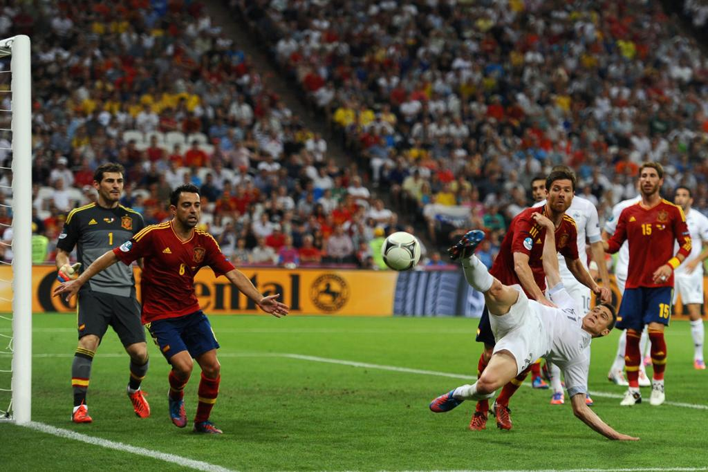 Laurent Koscielny of France in action as Xavi, Xabi Alonso and Iker Casillas of Spain look on.