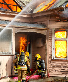 Members of the Woodend Fire Brigade practice a safe entry into a burning building.