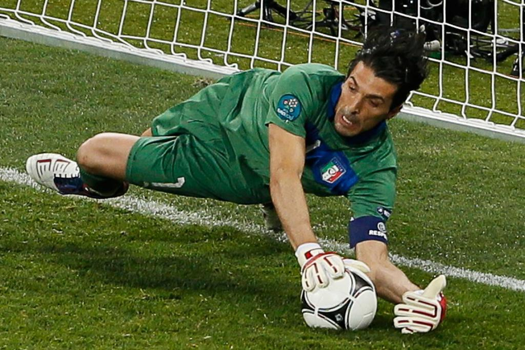Italian goalkeeper Gianluigi Buffon makes the decisive save of a penalty attempt by England's Ashley Cole.