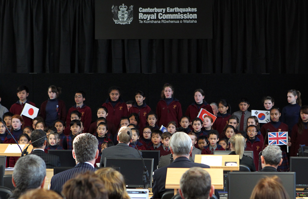 HEARING STARTS: Children from St Theresa's School sing two songs as a welcome at the royal commission hearing, and some hold flags to represent the 10 nationalities of people who were killed in the CTV building collapse.