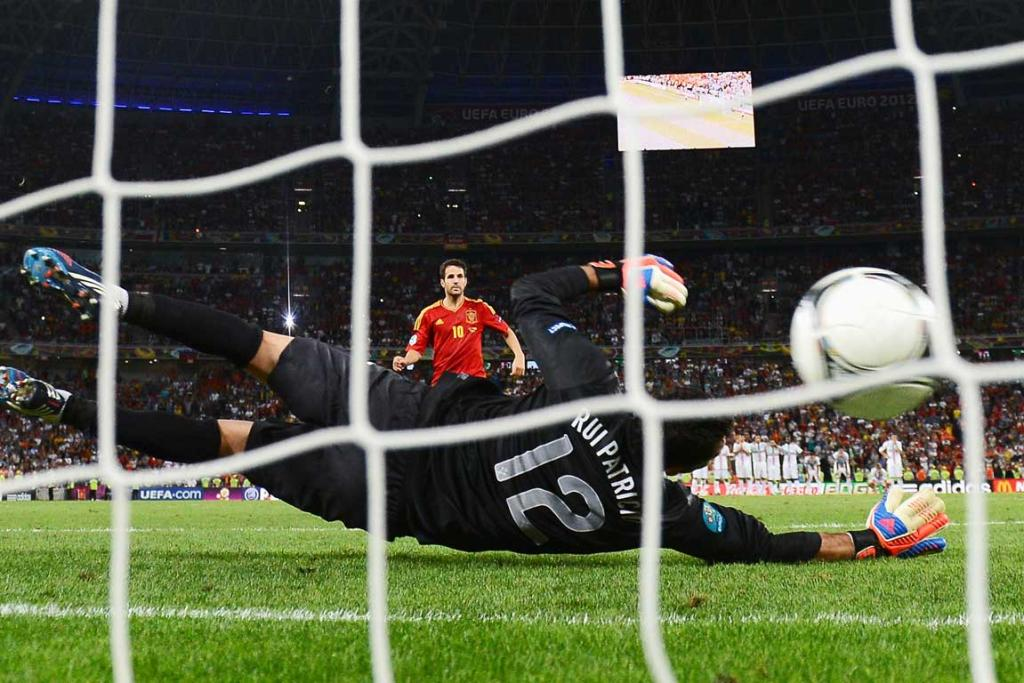 Cesc Fabregas of Spain scores the winning penalty past Rui Patrício of Portugal during their semi-final match.