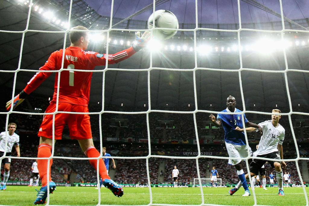 Mario Balotelli heads home the opening goal for Italy.