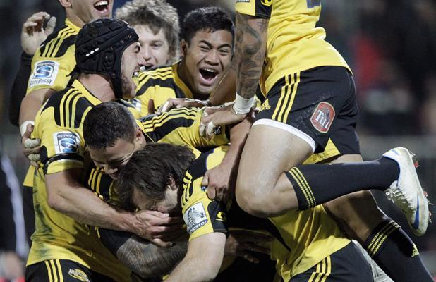 Hurricanes players celebrate their win against the Crusaders.