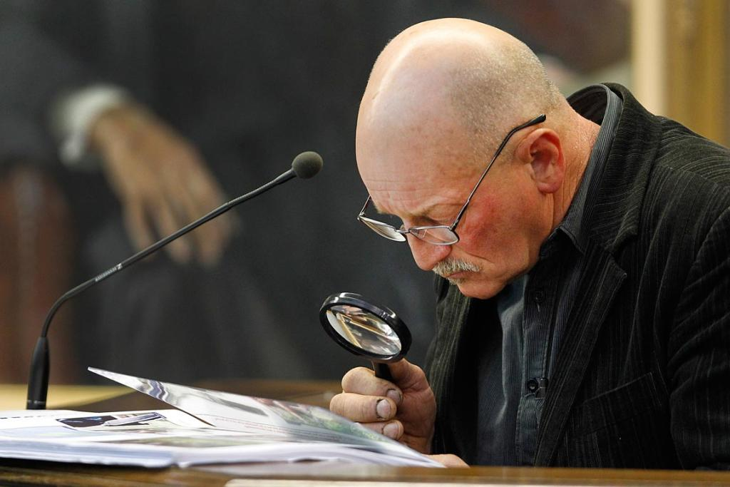 Witness Graeme Hunt uses a magnifying glass to examine photos of a hunting trip during his evidence to the jury.