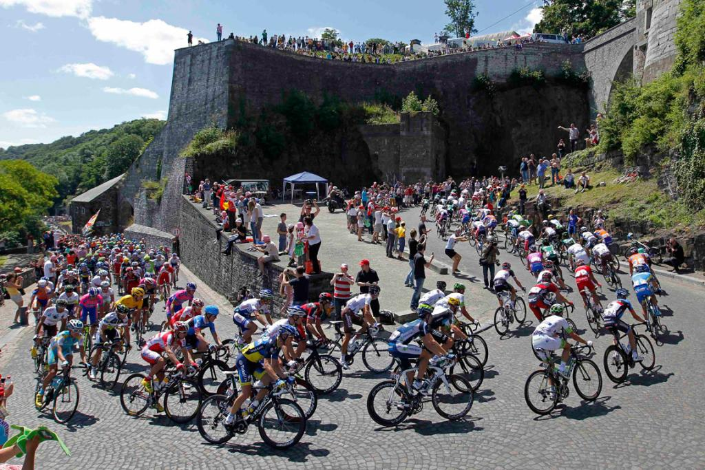 The pack of riders cycles past the citadel of Namur during the second stage of the Tour de France.