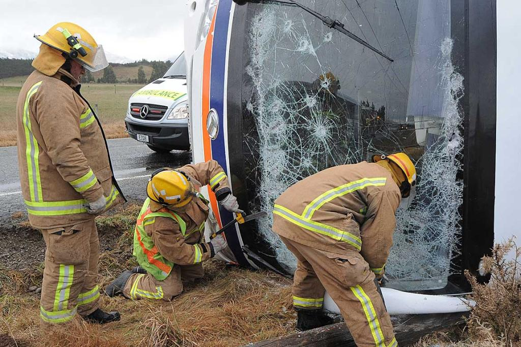 Firefighters cutting out the windscreen of the bus.