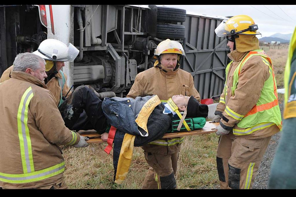 Fire officers move a man from the crash site.