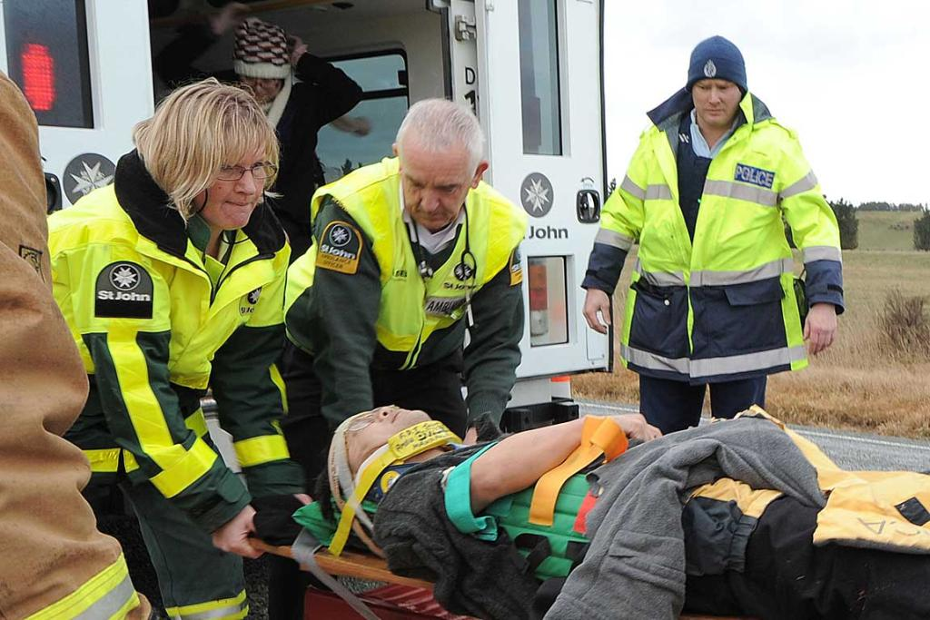 Ambulance staff prepare to move one of the injured to a helicopter.