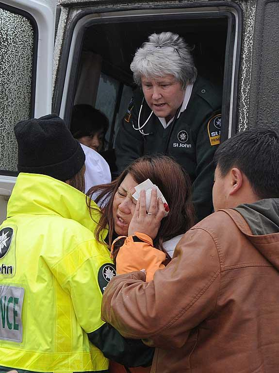 An injured woman is taken to an ambulance.