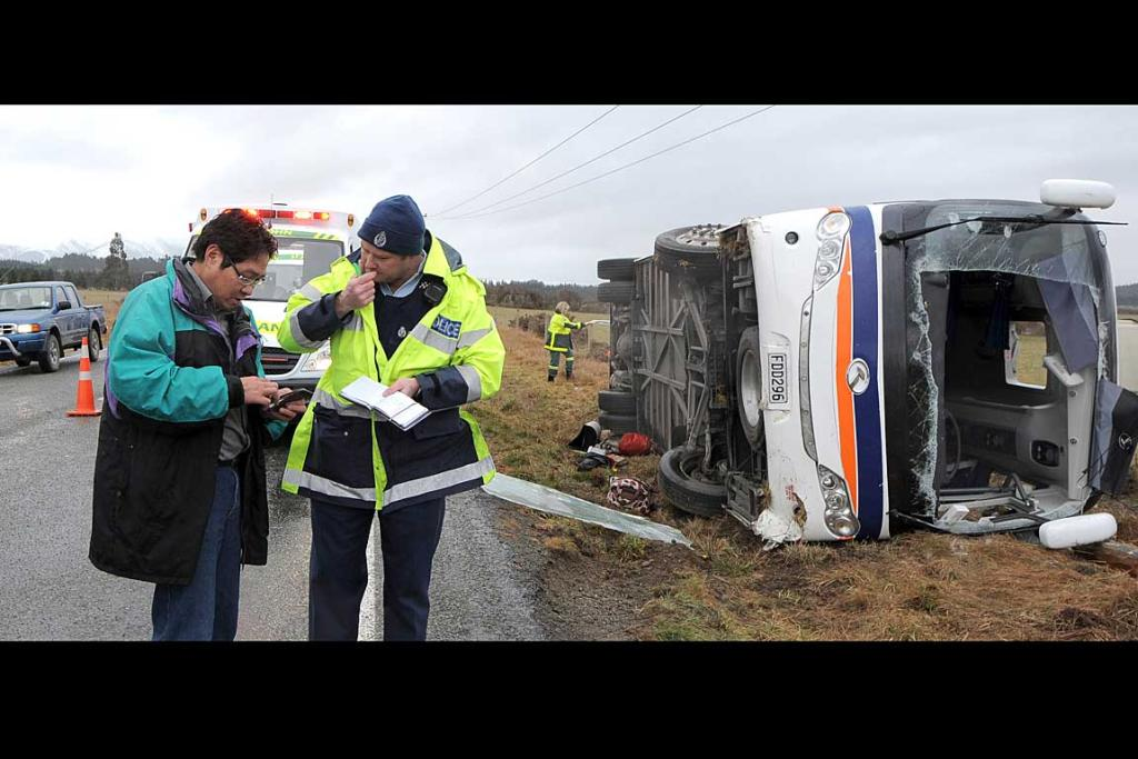 Police interview a bus driver who turned around to help those injured in the crash. This man was earlier incorrectly identified as the driver of the bus that crashed.