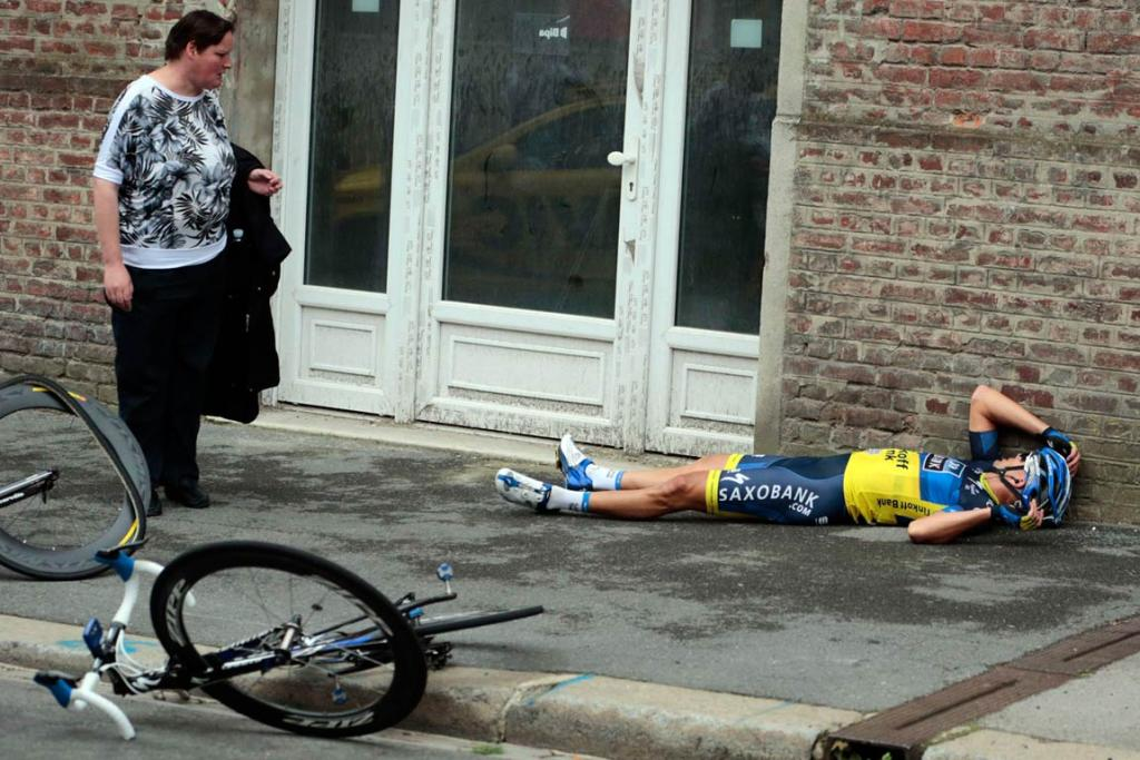 Australian Jonathan Cantwell lies on the footpath as a bystander looks on after a crash.