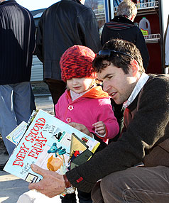 FRIDGE LIFE: Kevin Stack and his daughter, Natalie, 3, check out the children's books on offer at the Gap Filler book exchange on the corner of Kilmore and Barbadoes streets.