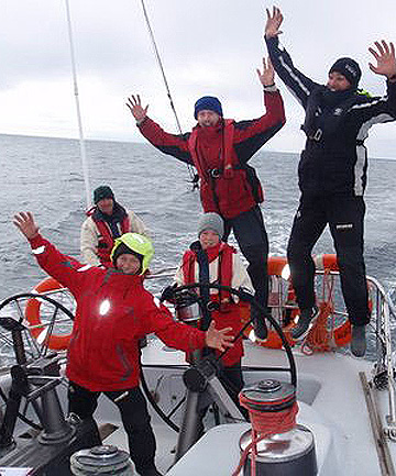 CRAZY CREW: Crew members Mike Baker, Kerry Roger, student Jacob Colligan, 14, at the helm, and skipper Thomas Collicott on board the Lion New Zealand.