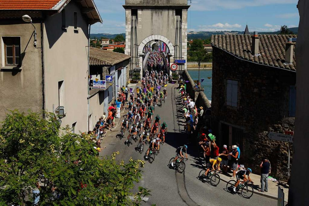 Bradley Wiggins of Great Britain in the race leader's yellow jersey leads the peloton over Le Rhone river during stage 12.