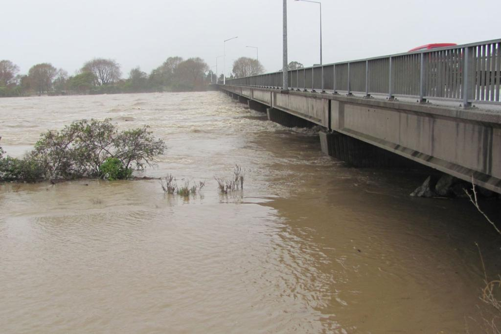 Floodwaters rise beneath the bridge across the Buller River on the southern entrance to Westport.