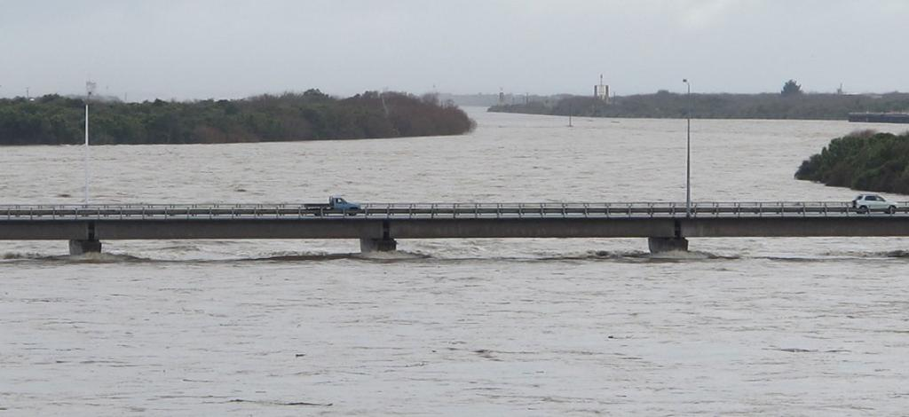Vehicles cross the bridge across the flooded Buller River on the southern approach to Westport.