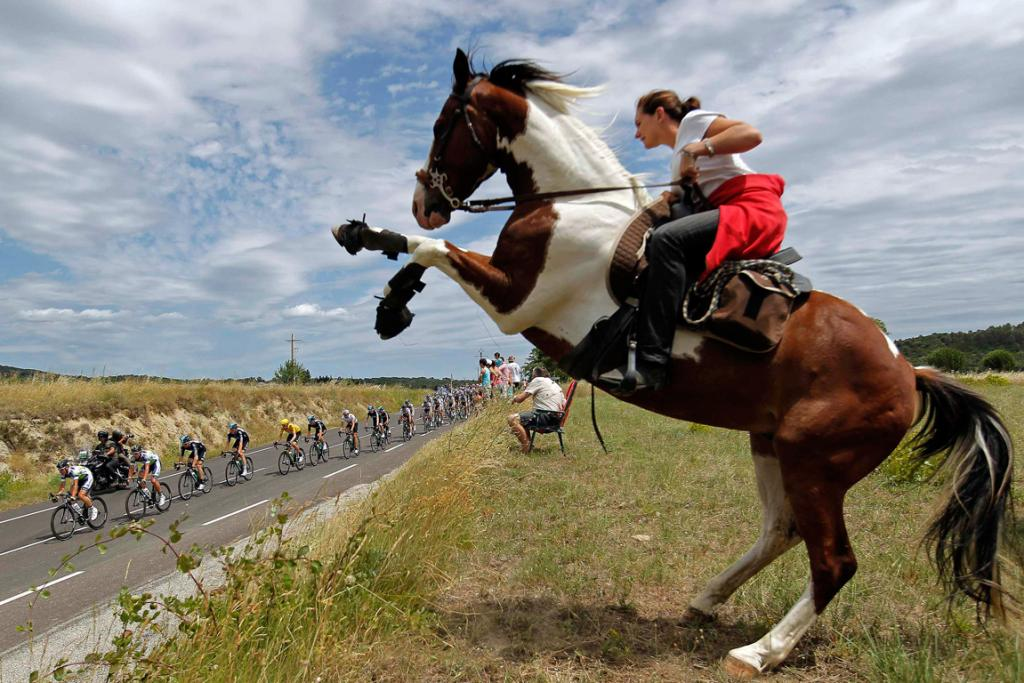The pack of riders cycles past a woman on a horse during the 13th stage of the 99th Tour de France.