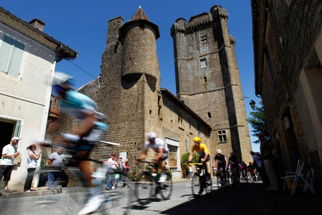 A pack of riders race through the village of Morlaas during the 15th stage.