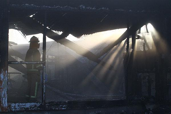 Fire staff inpsect what's left of a River Rd house gutted by fire overnight.