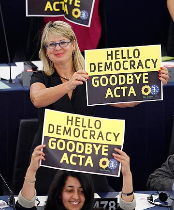 WATCHING THE SKYNETS: Members of the the Group of the Greens/European Free Alliance hold posters which reads 'hello democracy, goodbye ACTA' during a voting session on the Anti-Counterfeiting Trade Agreement at the European Parliament in Strasbourg on July 4, 2012.