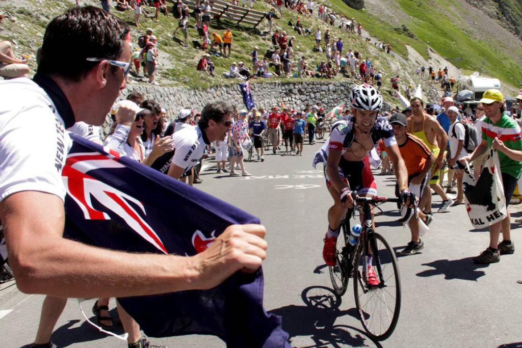 Greg Henderson is cheered on by a group of Kiwi fans as he pushes through the pain during stage 16.