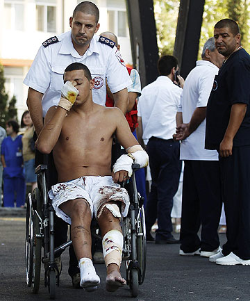 SURVIVOR: An man who survived a bomb attack on a bus full of Israeli tourists is taken to an ambulance as he leaves a hospital in Burgas, Bulgaria.