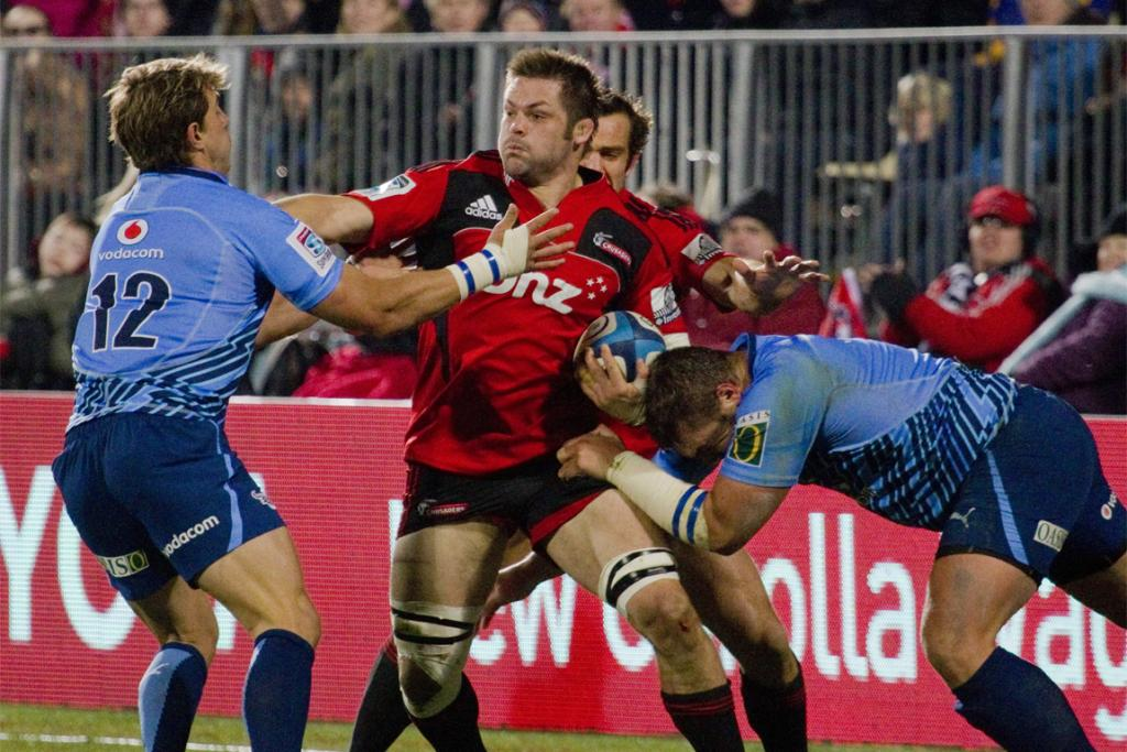 Richie McCaw is held in the tackle by the Bulls.