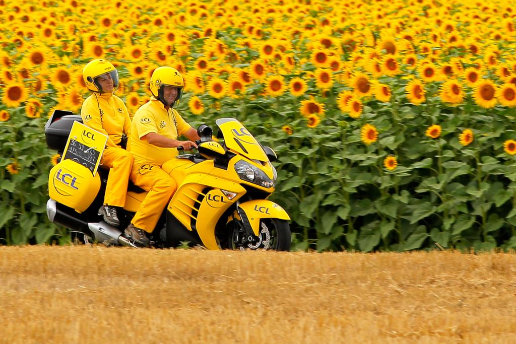 The time gap motorcycle passes through a field of sunflowers during stage 18.